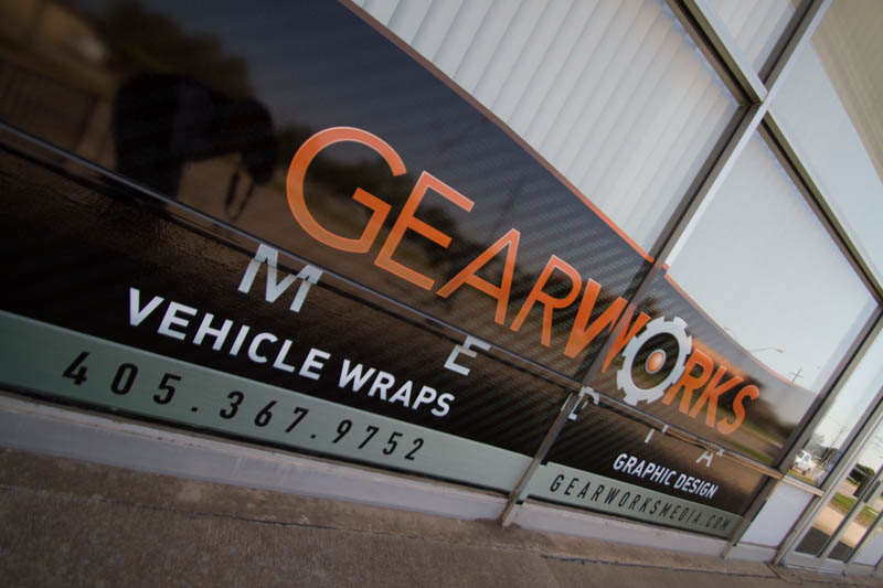 Gearworks Media glass window frontage with logo, graphic design & vehicle wraps text.