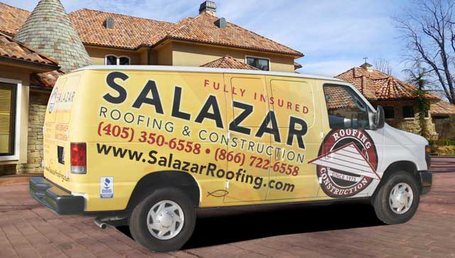 A van with a custom, yellow vehicle wrap for Salazar Roofing sitting in front of a house.