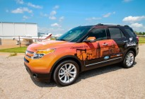 Front drivers view of a Ford Explorer with custom orange and black vehicle wrap