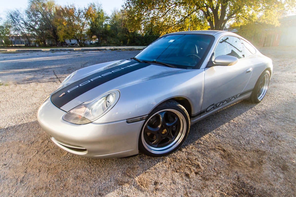 Carbon fiber vinyl stripes on the hood and rocker panel of a silver Porsche Carrera 996.