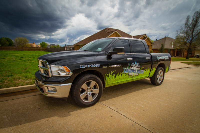 Partial vehicle wrap for Lawns Plus. Logo sitting in the grass on a black RAM D-1500.